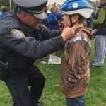 officer helping with helmet