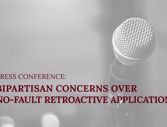 """Microphone with text """"Press Conference Addresses Bipartisan Support of No-Fault Lawsuit"""