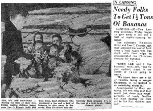 Newspaper clipping of Thomas Sinas and Lee Dramis handing out free bananas to Lansing community members.