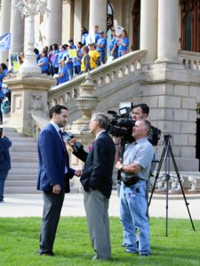 Steve Sinas being interviewed in front of Michigan capitol building